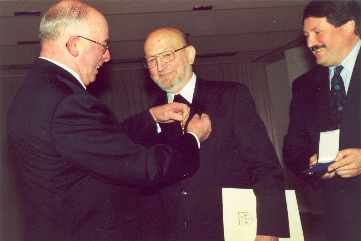 Landrat Meiners überreicht Pater Meyer-Schene 1999 das Bundesverdienstkreuz; rechts: Erster Kreisrat Winter