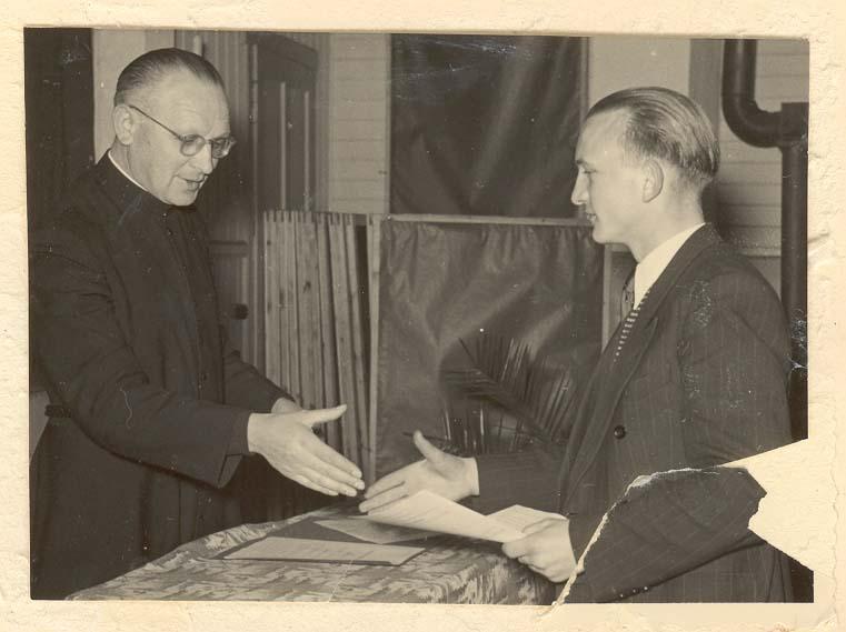 Pater Recker überreicht Josef Meyer-Schene das Abiturzeugnis